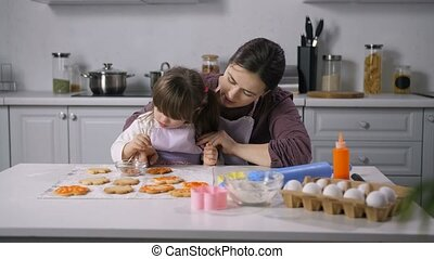 Positive little girl with down syndrome helping happy mother to decor freshly baked biscuits with royal icing in the kitchen. Caring mother developing child with special needs through teaching to cook
