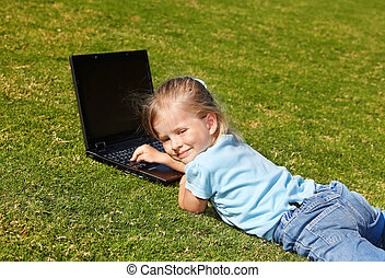 Kid with laptop outdoor.