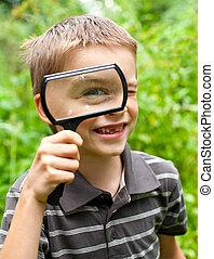 Cheerful boy looking through hand magnifier, shallow DOF