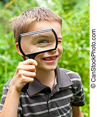 Kid with loupe - Cheerful boy looking through hand...