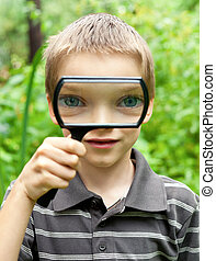 Young boy looking thru hand magnifier