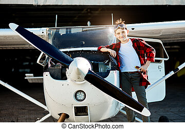 kid with screwdriver stands near single-engine propeller aircraft