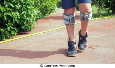 Slow motion steadicam shot of a child walking and wearing a system of functional electrical stimulation. Foot drop treatment
