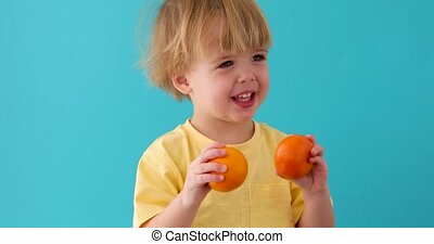 Kid with tangerines. small boy with mandarins. - Littele boy...