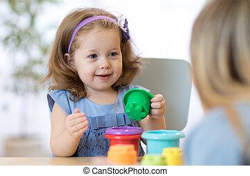 Kid with teacher in kindergarten