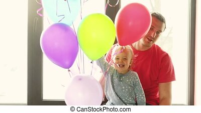 Kid with the daddy and balloons sit on window sill - Cute...