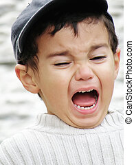 A kid is loudely shouting and yelling with wide opened mouth