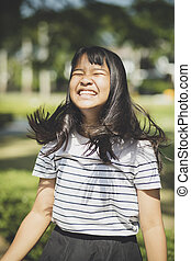 kidding face of asian teenager showns forelock hair flowing...