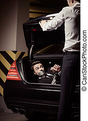 Kidnapped businessman. Tied up young man lying in the car trunk and looking at kidnapper