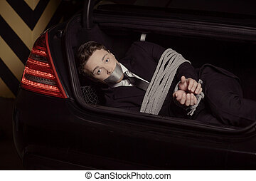 Kidnapped businessman. Tied up young men lying in the car trunk and looking at camera