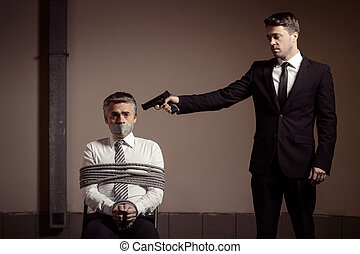 Kidnapper and victim. Tied up businessman sitting at the chair and looking at camera while young man in formalwear aiming him with gun