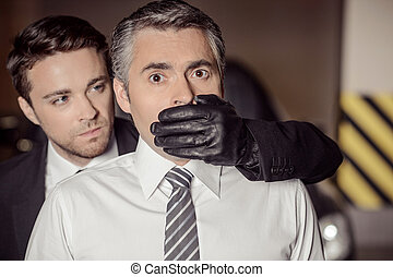 Kidnapping. Aggressive young men covering businessman mouth...
