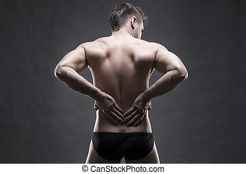 Kidney pain. Man with backache. Handsome muscular bodybuilder posing on gray background. Low key close up studio shot