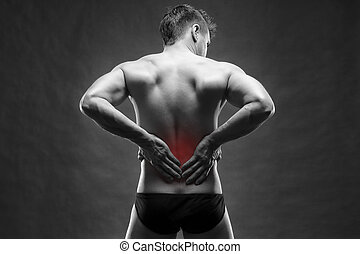 Kidney pain. Man with backache. Handsome muscular bodybuilder posing on gray background