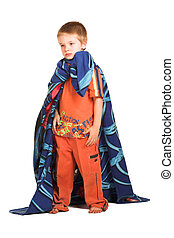 A boy wearing a blanket as a cape, looking sad.