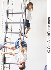 Kids Activity Concepts. Brother and Sister Playing Together During Physical Exercises on Wall Bars Indoors