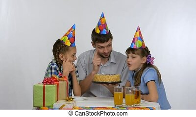Kids and dad have fun biting a birthday cake