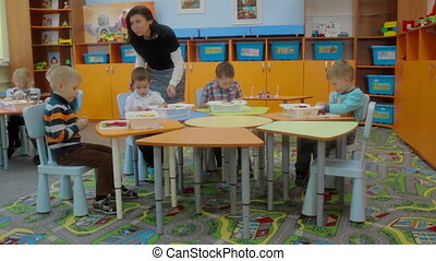 Kids and educator playing with plastic building blocks at...
