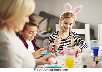 Kids and mature woman painting at the table