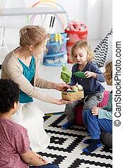 Little kids having fun with plush toys in kindergarten