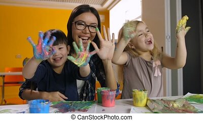 Kids and teacher with hands in paint at art lesson