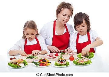 Kids and their mother preapring the party sandwiches