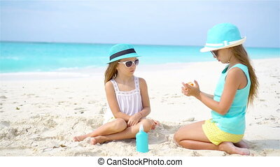 Kids applying sun cream to each other on the beach. The concept of protection from ultraviolet radiation