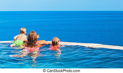 Kids at edge of infinity swimming pool with sea view.