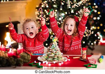 Kids baking on Christmas eve - Little boy and girl making...