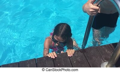 kids bathe in the pool water. children boy and girl swimming in the pool playing slow motion video