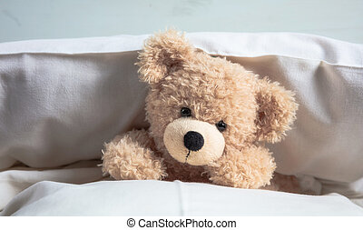Kids bedtime. Cute teddy playing with pillows in bed