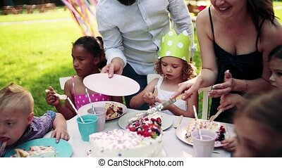 Kids birthday party outdoors in garden in summer, ...