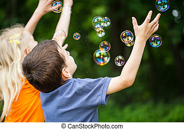 Kids blowing bubbles - Two kids having fun blowing bubbles ...