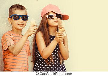 Kids boy and little girl eating ice cream.