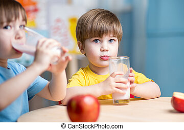 Kids boys drinking milk in nursery