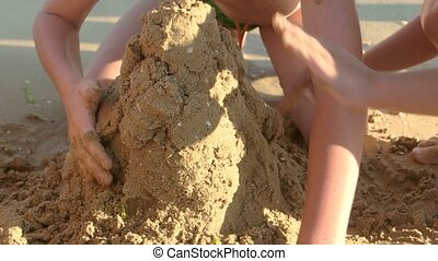 Kids building a sand structure.