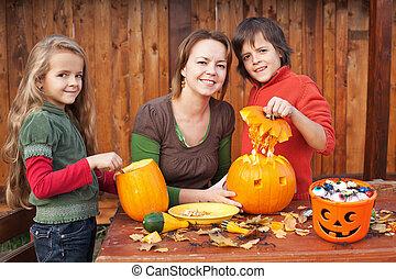 Kids carving jack-o-lanterns for Halloween