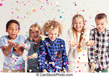 Kids catching confetti - Group of sweet young kids catching...