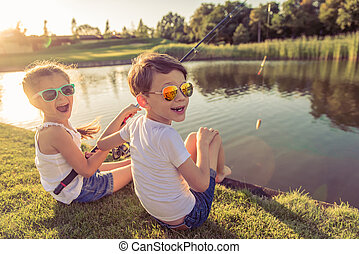 Kids catching fish - Funny stylish little boy and girl in...