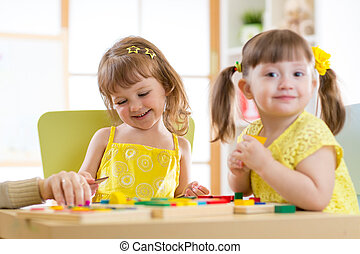 Kids children girls playing with educational child toys at home or daycare centre.