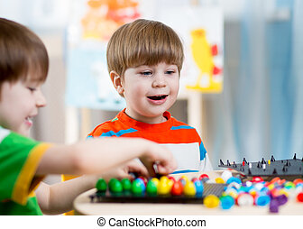 kids children playing mosaic game in kindergarten room