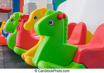 Kids colorful horse rocking chair on indoor playground for the kid's zone