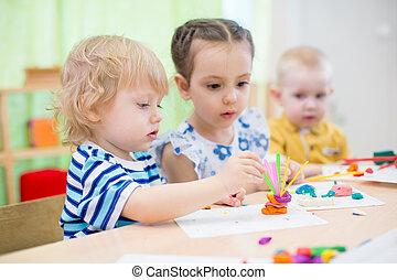 kids doing arts and crafts in kindergarten - kids modeling...