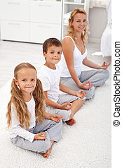 Kids doing yoga relaxation with their mother