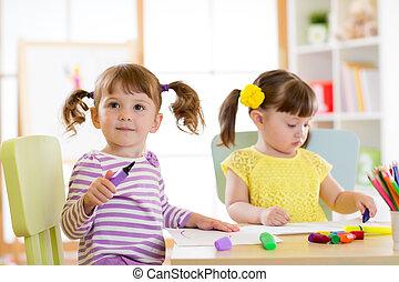Kids drawing in kindergaten. Children paint in nursery. Preschooler with pen at home. Creative toddler.