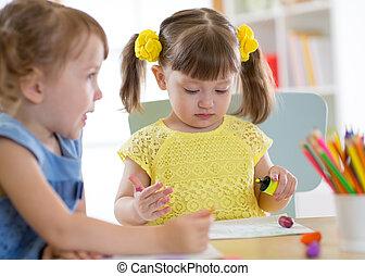 Kids drawing in kindergaten. Children paint in nursery. Preschooler with pencils at home. Creative toddlers.