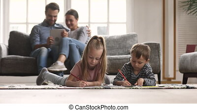 Kids drawing on floor parents relaxing on sofa at home