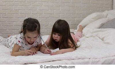 kids drawing pictures while lying on bed. pajama party and...