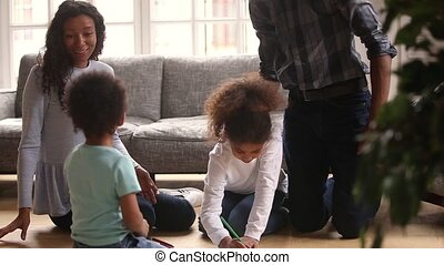 Kids drawing spending free time with parents on warm floor -...