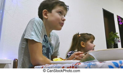 kids eat - boy teen at table eating meat chop holiday with...